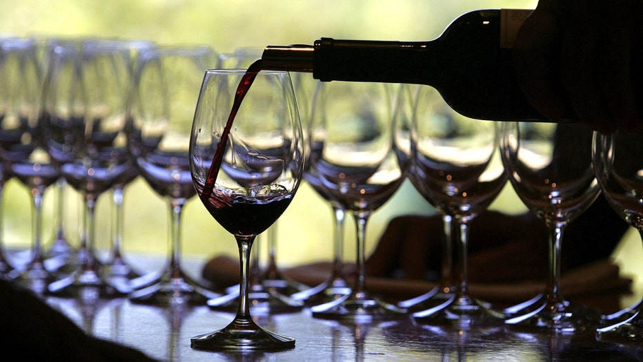 Bottle of red wine is poured into wine glasses.