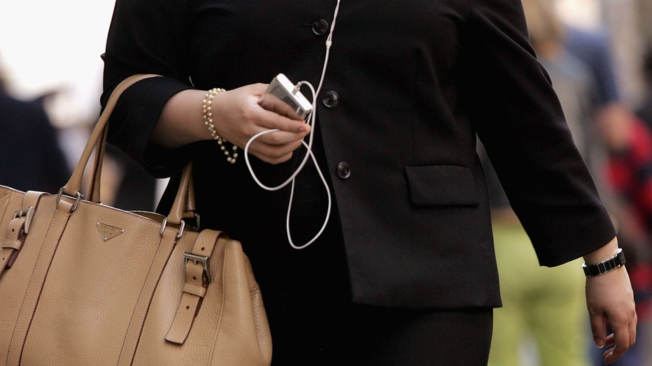 Woman walks down street holding purse and iPod.