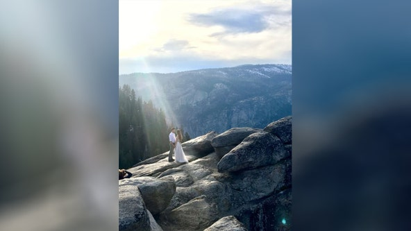 Woman searching for couple after capturing beam of light shining down during engagement photo shoot