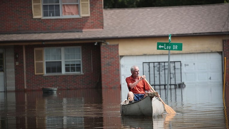 Warren Ryan canoes through floodwater from the Mississippi River to get to his home on June 1, 2019. (Photo by Scott Olson/Getty Images)