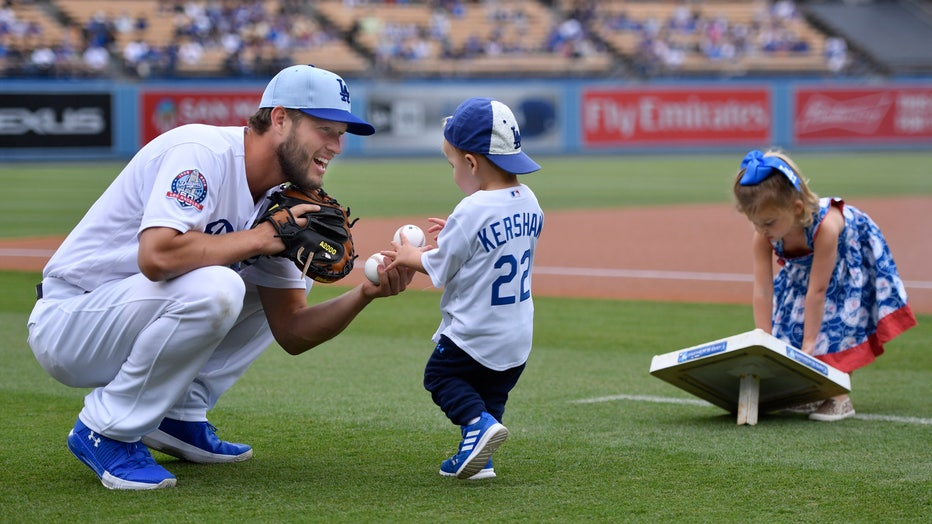 Clayton Kershaw #22 of the Los Angeles Dodgers plays with his children Charlie and Cali on Fathers Day before playing the San Francisco Giants at Dodger Stadium on June 17, 2018 in Los Angeles, California.