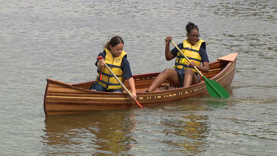 Students with Urban BoatWorks launch handcrafted boats on Cooper River Lake.