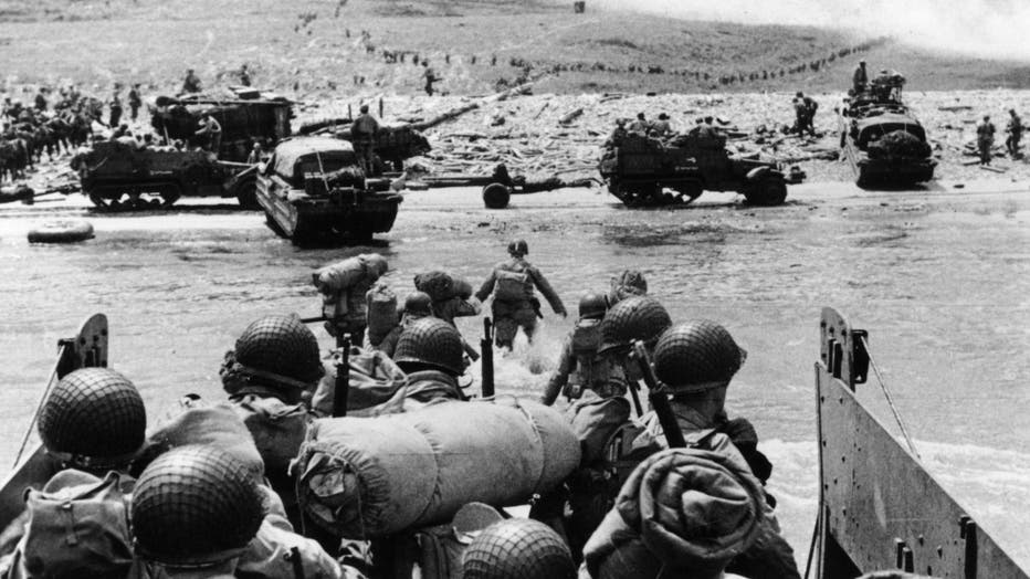 American assault troops and equipment landing on Omaha beach on the Northern coast of France, the smoke in the background is from naval gunfire supporting the attack.