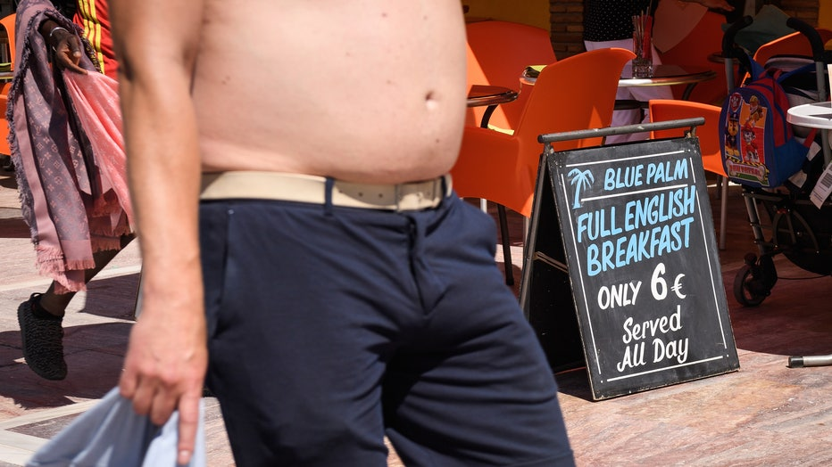 A shirtless man walks past a restaurant in this 2017 file photo. (Photo by Leon Neal/Getty Images)