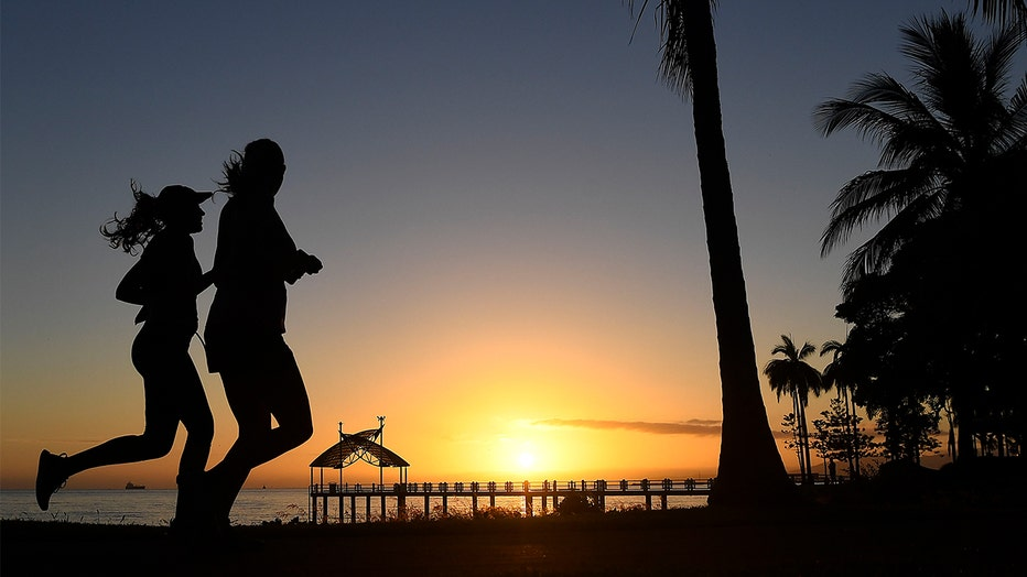 Two women are seen running along the Townsville Strand at sunrise in Townsville, Australia.