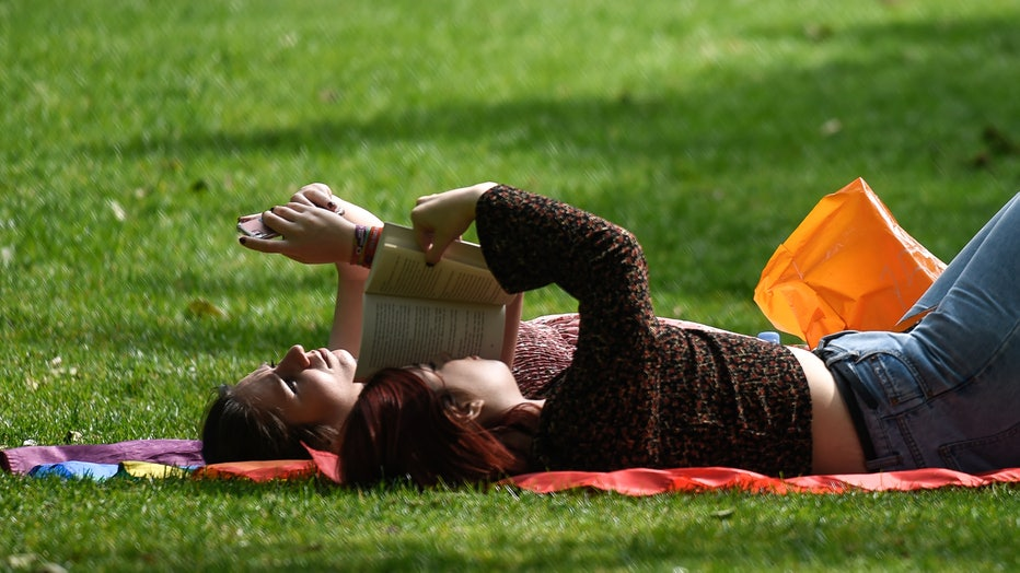 A woman reads a book next to her friend who is on her phone while relaxing in the sunshine in this file photo taken on May 15, 2019 in London, England.