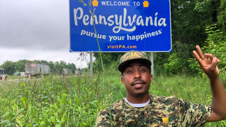 Rodney Smith Jr., a young black man, smiles in front of the Welcome to Pennsylvania sign on the state border. He is wearing a camouflage-colored hat and shirt.