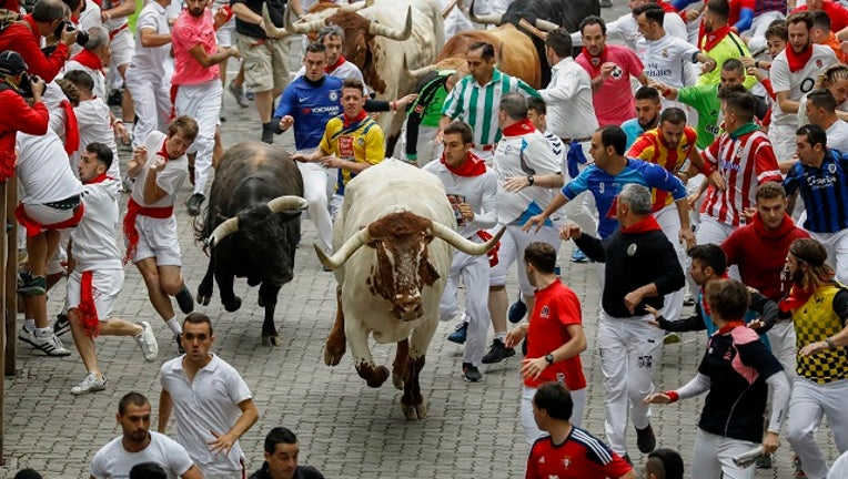 PAMPLONA, SPAIN - JULY 07: Revellers run with Puerto de San Lorenzo's fighting bulls before entering the bullring during the second day of the San Fermin Running of the Bulls festival. (Photo by Pablo Blazquez Dominguez/Getty Images)