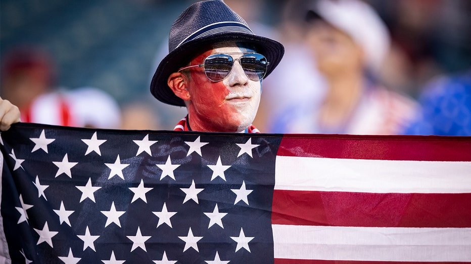 FILE: A fan with a face painted Red, White and Blue holds up the stars and stripes during the CONCACAF GOLD CUP Quarterfinal match of USA v Curacao at Lincoln Financial Fieldin Philadelphia, Pennsylvania