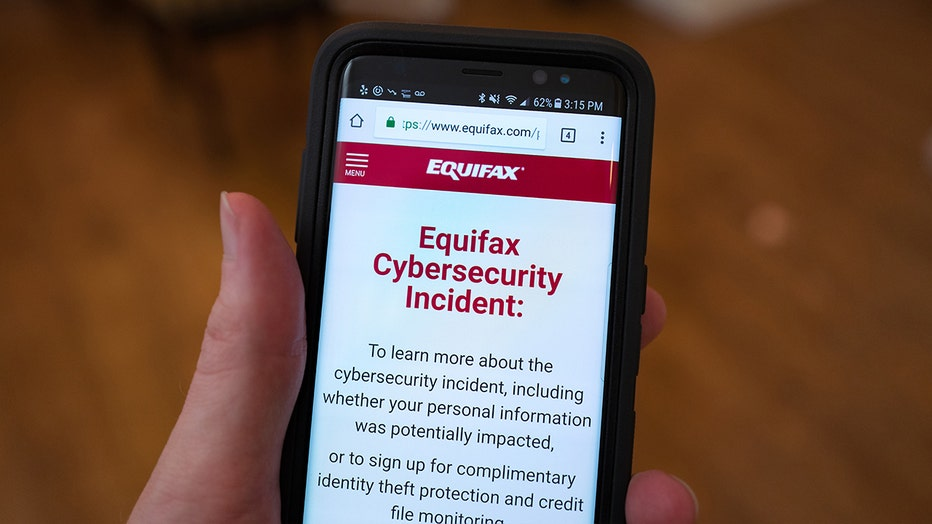A mobile phone is held open to the Equifax website following the2017 security breach that led to 147 million people's data being compromised.