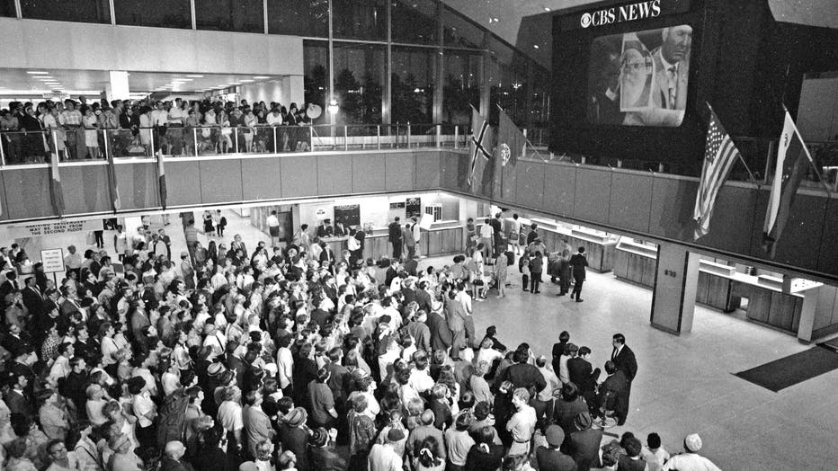 As Old Glory hangs over them, thousands of passengers and workers at Kennedy Airport International Arrivals Building stand or sit in awe as they watch on giant TV screen another American flag being raised on the moon. The crowd stands three deep on the balcony of building. Earlier, as the Eagle touched down on the moon's Sea of Tranquility, the atmosphere at the airport was anything but tranquil as the thousands whooped and cheered for their heroes.