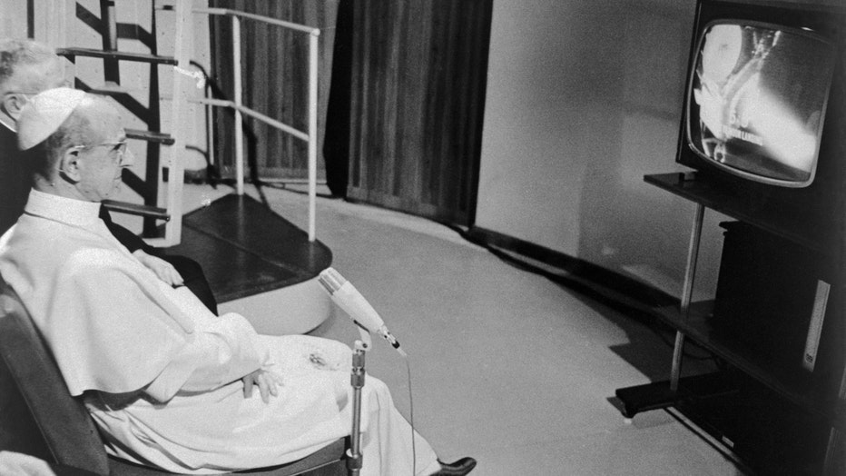 Pope Paul VI sits before a television set in his summer villa and watches the astronauts Neil Armstrong and Buzz Aldrin land on the moon.