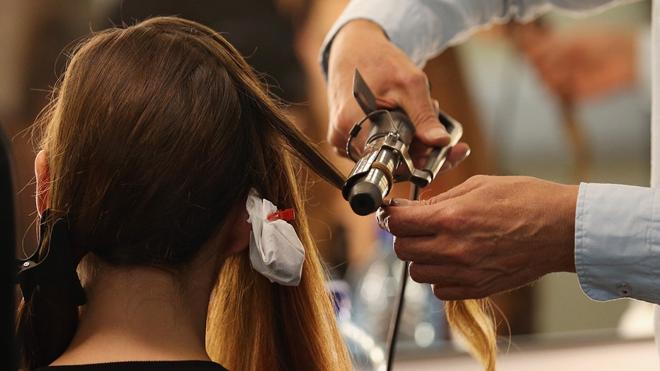 FILE: A model gets her hair curled. In extremely rare cases, hair grooming can cause seizure-like reactions in children.