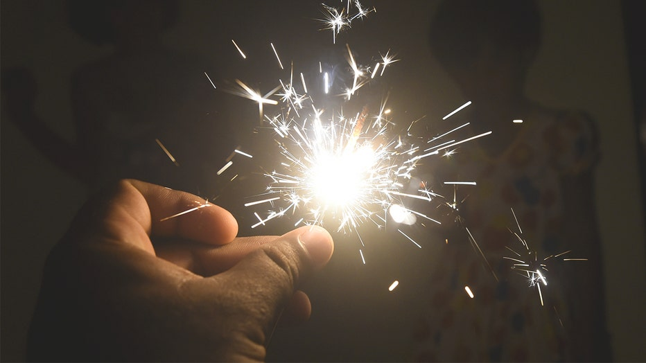 A burning sparkler is held. The chemicals in sparklers and other fireworks can cause serious harm to pets if ingested.