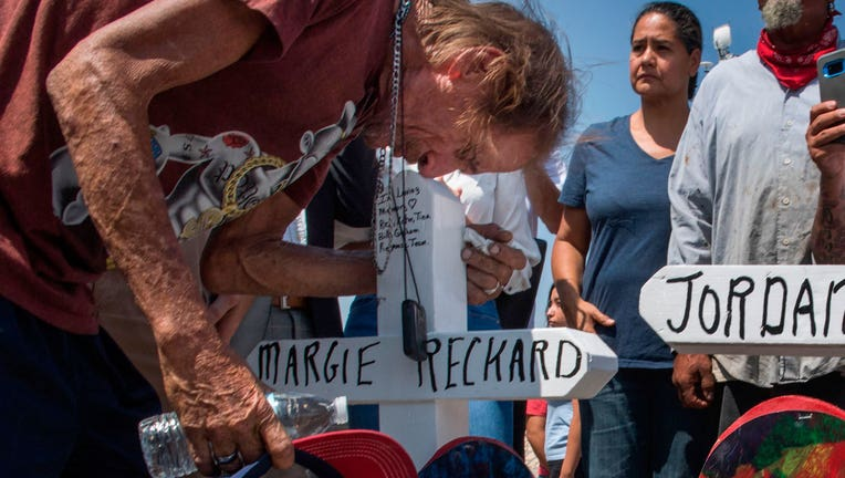 Antonio Basbo kisses the cross with the name of his common-law wife Margie Reckard, who died in El Paso shooting, at a makeshift memorial in El Paso, Texas, on August 5, 2019.