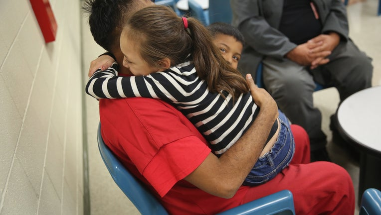 ADELANTO, CA - NOVEMBER 15: An immigrant detainee holds his children during a family visitation visit at the Adelanto Detention Facility on November 15, 2013 in Adelanto, California. The facility, the largest and newest Immigration and Customs Enforcement (ICE), detention center in California, houses an average of 1,100 immigrants in custody pending a decision in their immigration cases or awaiting deportation. The average stay for a detainee is 29 days. The facility is managed by the private GEO Group. ICE detains an average of 33,000 undocumented immigrants in more than 400 facilities nationwide.