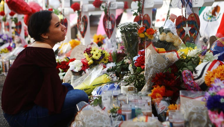 A woman stands by a growing memorial set up outside of a Walmart in El Paso, Texas, where 22 people were killed in a mass shooting.