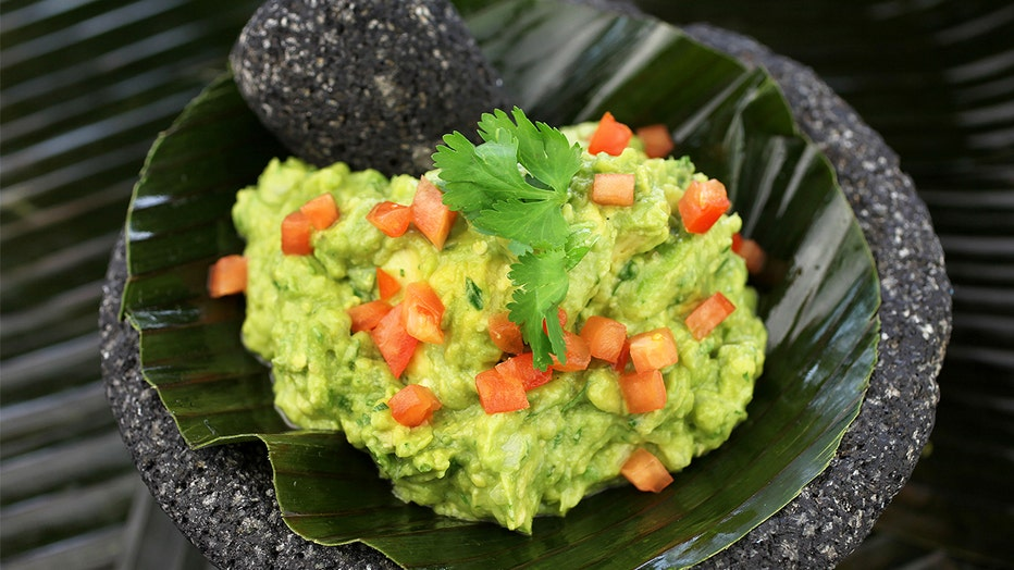 FILE: A bowl of guacamole is served in a mortar with pestle. Surging avocado prices this summer have caused some restaurants to serve