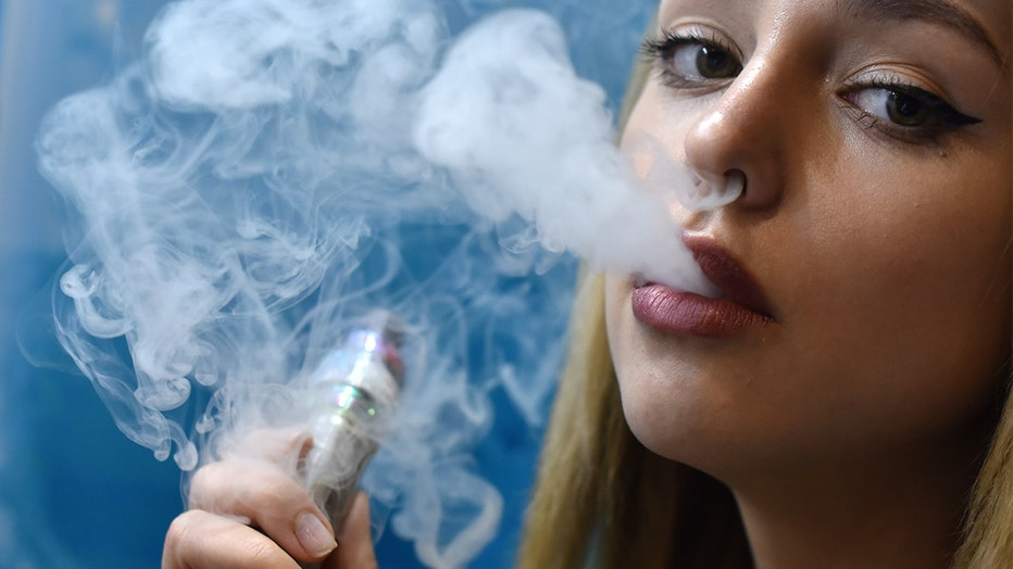 A promoter puffs from an e-cigarette while working at a stand during Vape Jam 2019.