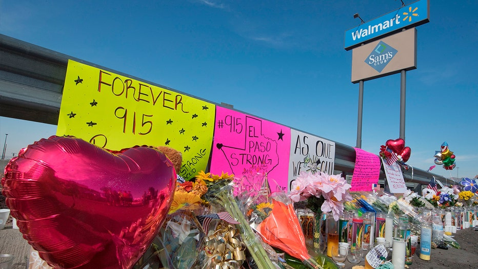 Flowers and signs at a makeshift memorial outside the El Paso, Texas, Walmart where a mass shooting occurred Saturday. Walmart has said that it will continue to sell guns and ammunition.