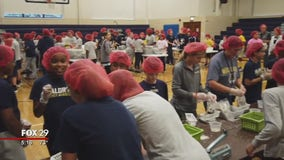 Students at Waldron Mercy Academy pack meals to feed the hungry