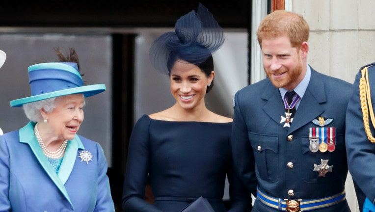 ) Queen Elizabeth II, Meghan, Duchess of Sussex and Prince Harry, Duke of Sussex watch a flypast to mark the centenary of the Royal Air Force from the balcony of Buckingham Palace on July 10, 2018 in London, England.
