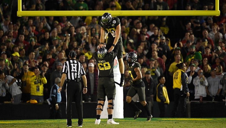 PASADENA, CALIFORNIA - JANUARY 01: Justin Herbert #10 of the Oregon Ducks celebrates with Penei Sewell #58 after scoring a 30 yard touchdown against the Wisconsin Badgers during the fourth quarter in the Rose Bowl game presented by Northwestern Mutual at Rose Bowl on January 01, 2020 in Pasadena, California. (Photo by Kevork Djansezian/Getty Images)