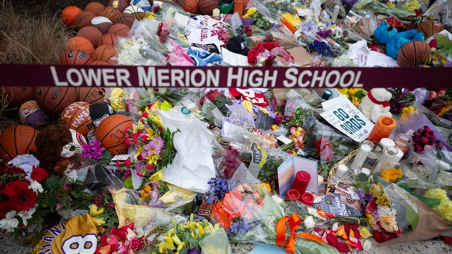 Basketballs, flowers, letters, and jerseys are left at a memorial for Kobe Bryant after he was killed in a helicopter crash, at Lower Merion High School.