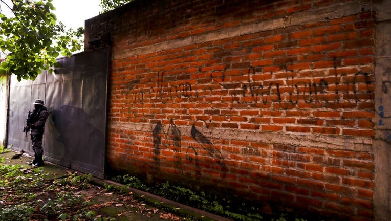 A police guard stands next to a graffiti wall with the name of a gang as part of a routine patrol in Lourdes, La Libertad, El Salvador.