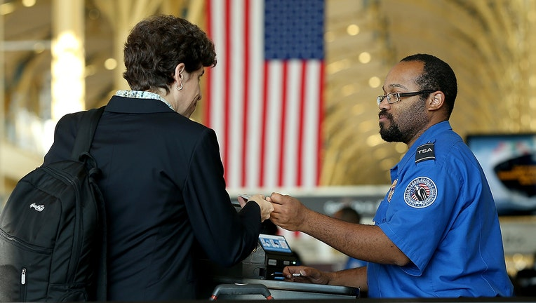 A TSA officer checks travel documents for passengers traveling through Reagan National Airportin Arlington, Virginia. Starting October 1, 2020, passengers will need REAL ID-compliant identification for air travel.