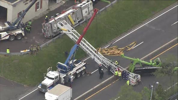 Fire truck displaying American flag overturns onto roadway in Bucks County