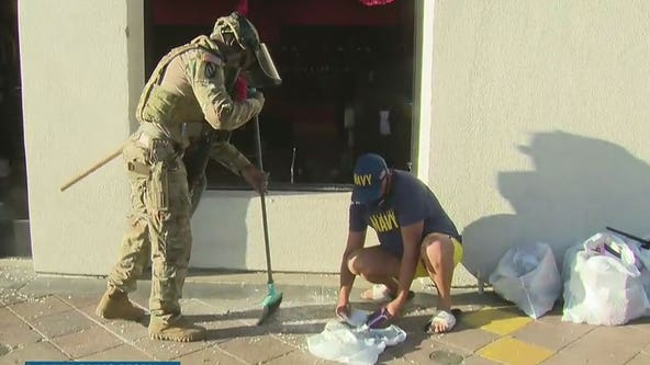 Members of the National Guard help community members clean up Long Beach following night of unrest