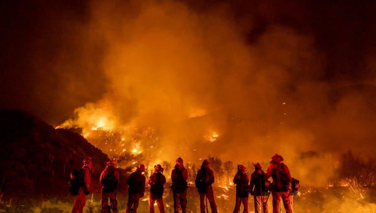 September 9: A group of inmate firefighter watch as the El Dorado Fire burns a hillside near homes in Mountain Home Village, California, inside the San Bernardino National Forest, September 9, 2020.