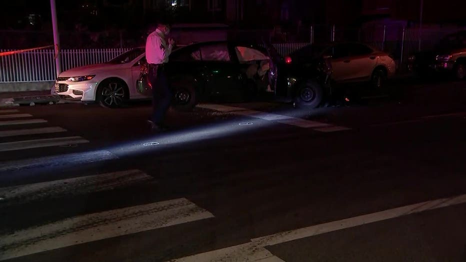 Investigators survey the scene after a woman was shot and later involved in a car crash in Juniata Park.