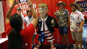 Gold-colored Trump statue at CPAC drawing crowds