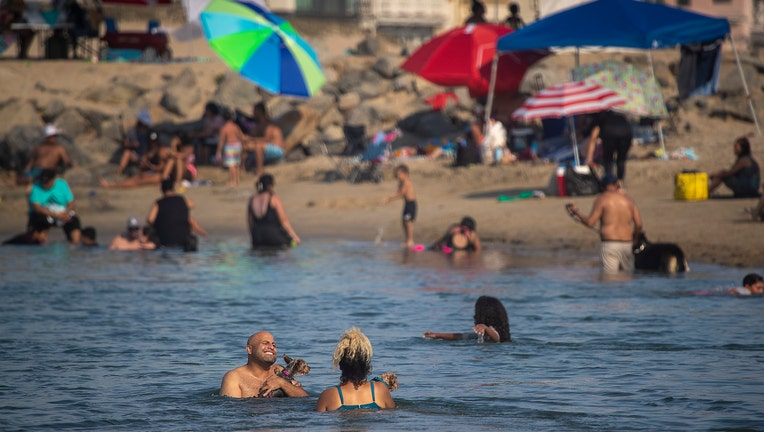 Amid a heat wave, Labor Day weekend beach-goers take to the cool ocean waters at the Santa Ana River County Beach River Jetties