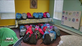 Young girl continues filling backpacks with school supplies