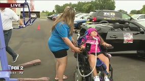 D-MAN giving convertible rides to those in wheelchairs at Dream Cruise
