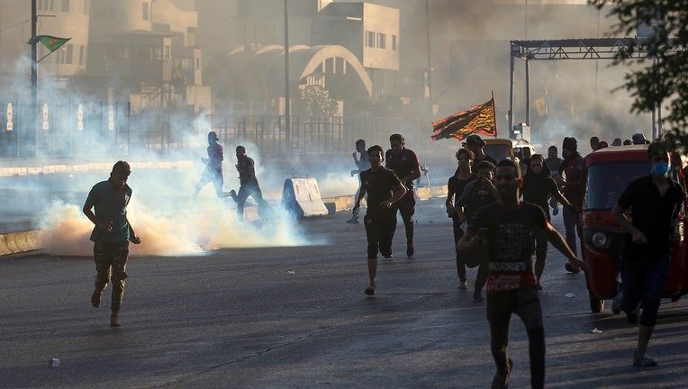 Iraqi protesters rush for cover from teargas fired by security forces during a demonstration against state corruption, failing public services, and unemployment, in the Iraqi capital Baghdad on October 5, 2019. - Renewed protests took place under live fire in Iraq's capital and the country's south Saturday as the government struggled to agree a response to days of rallies that have left nearly 100 dead. The largely spontaneous gatherings of demonstrators -- whose demands have evolved since they began on Tuesday from employment and better services to fundamental government change -- have swelled despite an internet blackout and overtures by the country's elite. Hours after a curfew in Baghdad was lifted on Saturday morning, dozens of protesters rallied around the oil ministry in the capital, facing live rounds fired in their direction, an AFP photographer said. (Photo by AHMAD AL-RUBAYE / AFP) (Photo by AHMAD AL-RUBAYE/AFP via Getty Images)