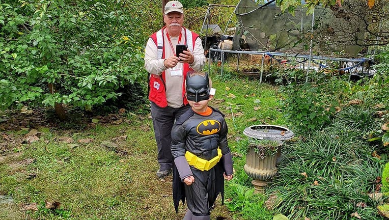 """One kindhearted sheriff's officer in North Carolina wanted to ensure a local boy could enjoy a """"normal as possible"""" Halloween after the child's family lost their home and belongings in a devastating fire. The deputy surprised the youngster with a Batman costume to replace the outfit destroyed in the blaze. (Edneyville Fire and Rescue)"""