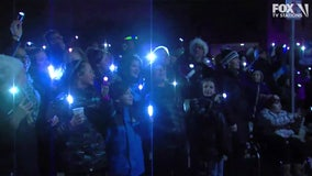 Community spreads holiday cheer by waving lights outside pediatric hospital