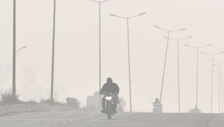 FILE - A man rides a motorcycle amid heavy smog on a winter morning, at Zakhira, on November 30, 2019 in New Delhi, India.