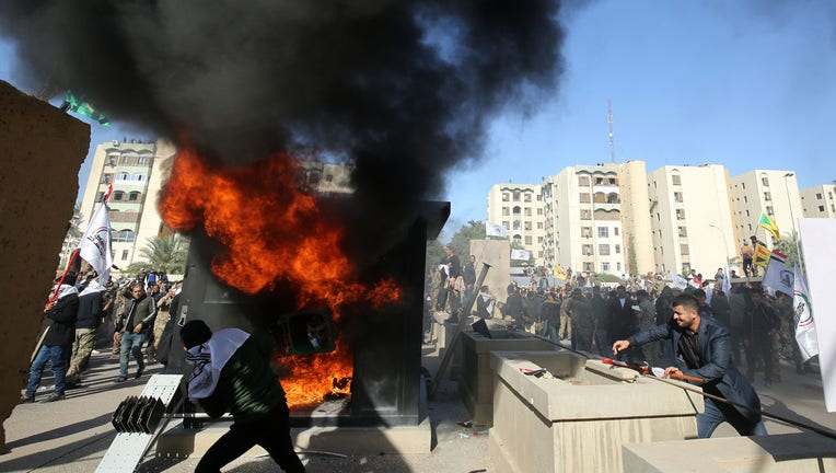 Iraqi protesters set ablaze a sentry box in front of the US embassy building in the capital Baghdad to protest against the weekend's air strikes by US planes on several bases belonging to the Hezbollah brigades near Al-Qaim, an Iraqi district bordering Syria, on December 31, 2019. (Photo by Ahmad AL-RUBAYE / AFP) (Photo by AHMAD AL-RUBAYE/AFP via Getty Images)