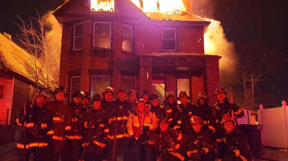 A photo of a group of firefighters in front of a raging house fire