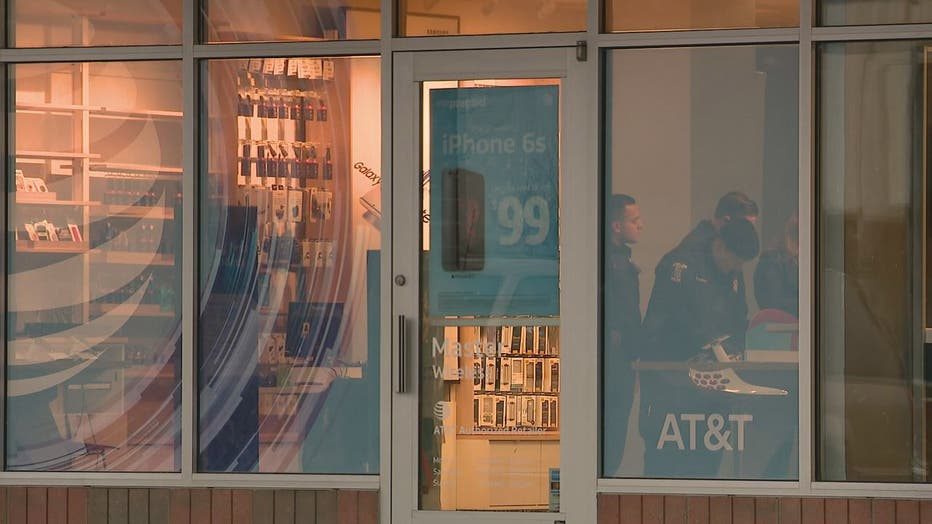 Policemen are seen through the storefront window of the AT&T shop in Sterling Heights.