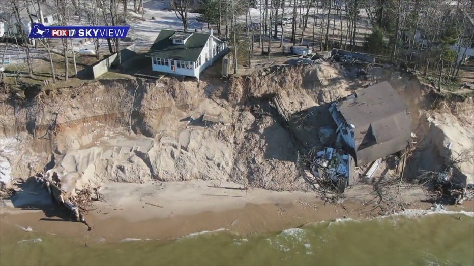 Drone footage shows a cottage collapsed at the bottom of a beachside cliff