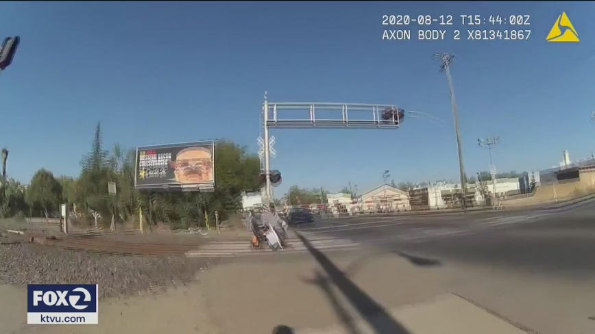 VIDEO: California police officer whisks man in wheelchair off train tracks just in time