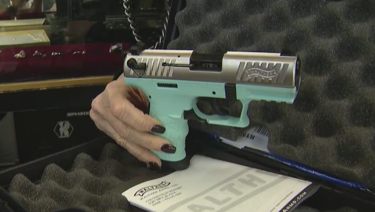 A woman holds a tiffany blue colored handgun