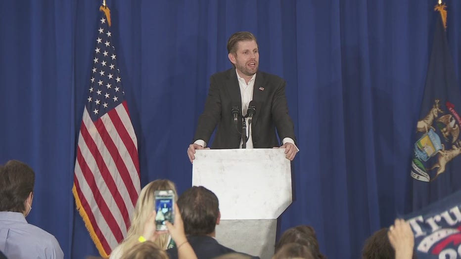 Eric Trump speaks behind a podium on a stage.