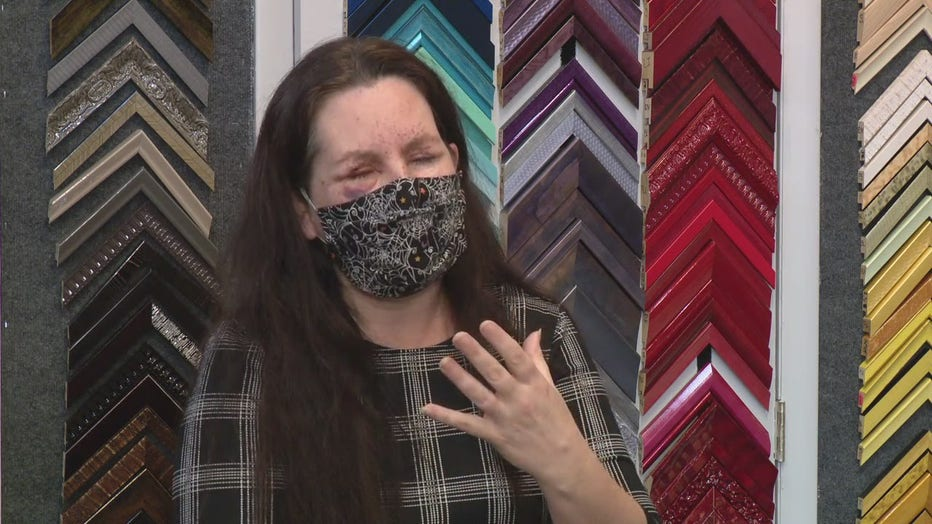 Cindy Eckley wears a cloth mask over her nose and face and stands in front of a frame shop, with damage to her eyes
